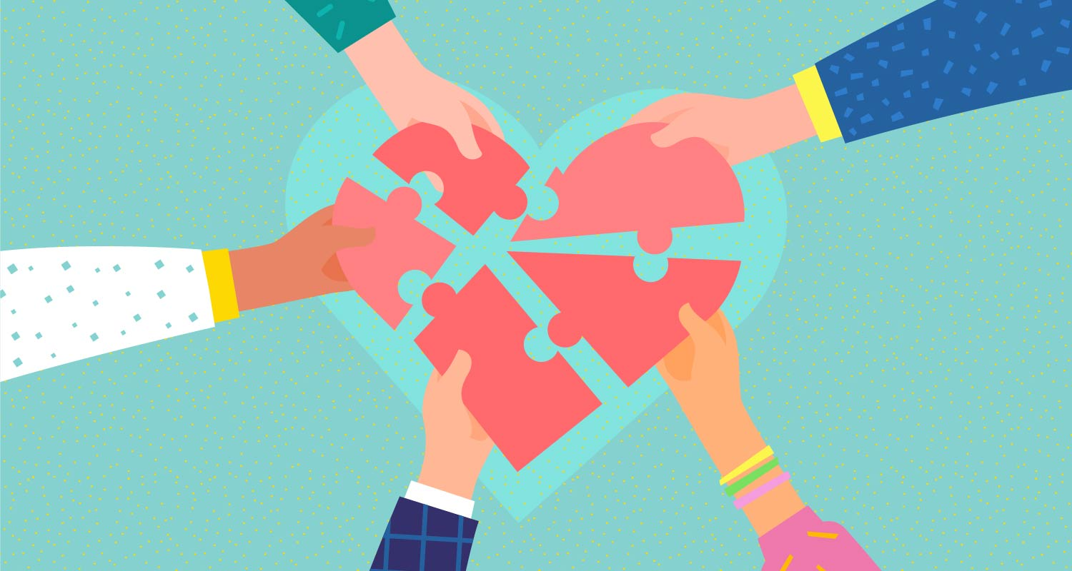 Hands piecing together a heart puzzle