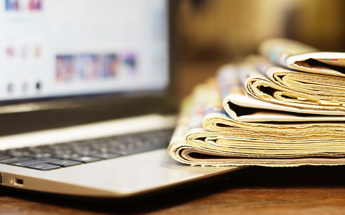 Stack of newspapers with laptop
