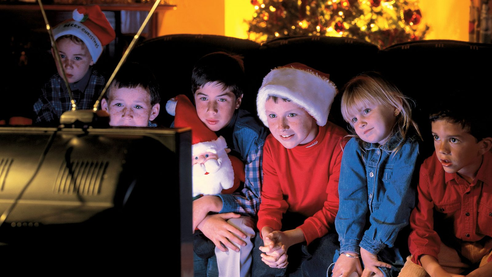 Kids in holiday accessories watching TV
