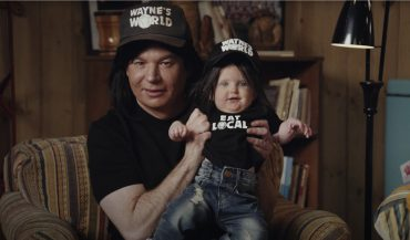 Wayne of Wayne's World holding a baby in Uber Eats Super Bowl commercial