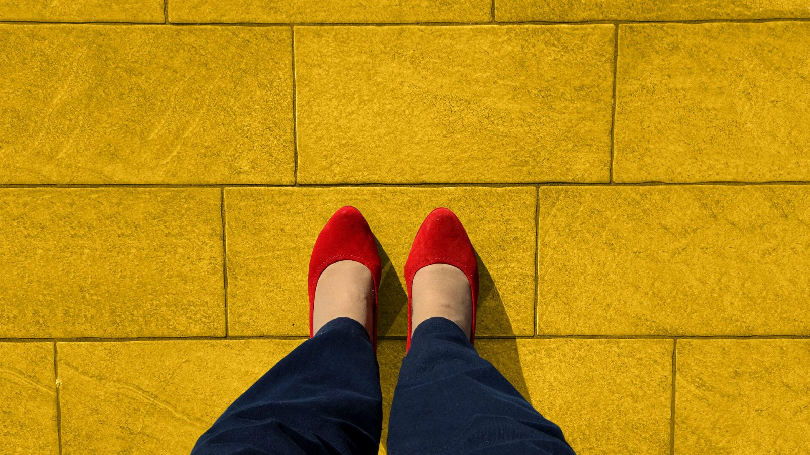 Overhead view of legs and red shoes on yellow road